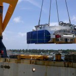 Cutterhead of Tunnel Boring Machine is hoisted from the ship's hold to barge